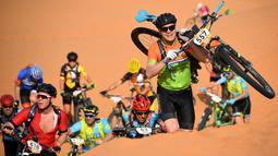 Para pebalap memanggul sepeda mereka menaiki gundukan pasir pada etape 1 edisi ke 14 balap sepeda gunung Titan Gurun 2019 di sekitar Kota Merzouga, Maroko, Minggu (28/4/2019). Trek Titan Gurun 2019 sepanjang 640 km menghubungkan antara Merzouga dan Maadid. (Franck Fife / AFP)