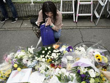Seorang wanita berdoa untuk para korban kebakaran  di gedung Kyoto Animation Studio di Kyoto, Jepang (19/7/2019). Korban tewas kebakaran di studio animasi di Kyoto, Jepang bertambah menjadi 33 orang. Motif pembakaran yang disengaja ini masih diselidiki otoritas setempat. (AP Photo/Jae C. Hong)