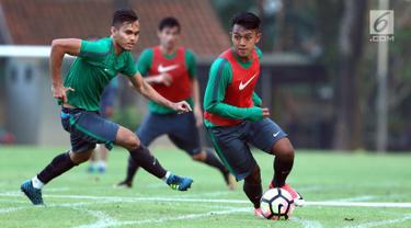 Pemain Timnas Indonesia U-22, Febri Hariyadi (kanan) berebut bola dengan M Rezaldi Hehanusa saat latihan di lapangan SPH Karawaci, Banten, Senin (7/8). Latihan ini persiapan laga di SEA Games 2017 Kuala Lumpur. (Liputan6.com/Helmi Fithriansyah)