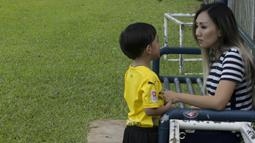 Anak dari Stefano Teco, yang bernama Romario, bersama ibunya, Miranda, saat latihan Persija Jakarta di Lapangan Sutasoma, Jakarta, Minggu (25/2/2018). Ketika ayahnya bekerja sang anak asyik bermain sepak bola. (Bola.com/Aspirilla Dwi Adha)