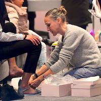 Rela duduk di lantai, aktris ini manjakan pelanggan yang setia membeli brand sepatunya.