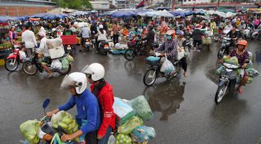 Orang-orang mengendarai sepeda motor melewati pasar di Phnom Penh (24/7/2020). Pasar membentuk bagian integral dalam kehidupan orang Kamboja, dengan kunjungan harian yang dilakukan untuk persediaan makanan untuk hari itu serta barang-barang lainnya. (AFP/Tang Chhin Sothy)