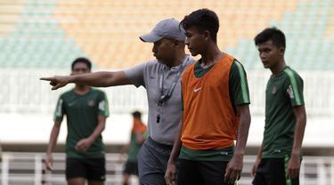 Pelatih Timnas Indonesia U-19, Fakhri Husaini, memberikan arahan kepada Mochammad Supriadi saat latihan di Stadion Pakansari, Bogor, Rabu (2/10). Latihan ini merupakan persiapan jelang AFF U-19 di Vietnam. (Bola.com/Yoppy Renato)