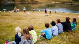 Anak-anak melihat permainan 'Gilihuesine' di resor alpine Bettmeralp, Swiss (16/9). Permainan tradisional Gilihuesine diikuti oleh enam pemain dimana pemain dapat mendapatkan tulang saat dipukul. (Valentin Flauraud/Keystone via AP)