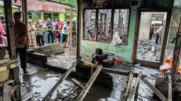 Warga berkerumun di sekitar lokasi kebakaran pabrik korek gas di Binjai, Langkat, Sumatera Utara, (21/6/2019). Korban tewas dalam kebakaran tersebut terdiri dari ibu rumah tangga dan anak-anak. (Ivan Damanik/AFP)