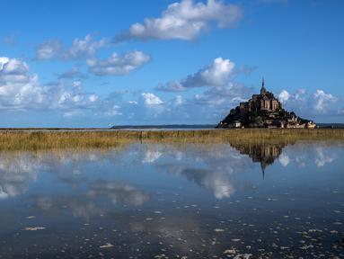 Kastil Mont Saint-Michel terlihat di Normandia, Prancis barat laut (1/9/2019). Mont Saint-Michel adalah sebuah pulau pasang berbatu di Normandi, sekitar satu kilometer dari pesisir utara Prancis di mulut sungai Couesnon dekat Avranches. (AFP Photo/Joel Saget)