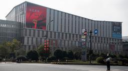Pria bermasker berdiri dekat supermarket Alibaba di Kota Hangzhou, Provinsi Zhejiang, China, Rabu (5/2/2020). Pemerintah Hangzhou memberlakukan pembatasan pergerakan bagi warganya menyusul mewabahnya virus corona. (NOEL CELIS/AFP)