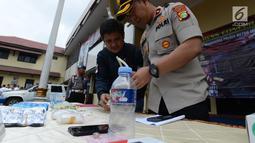 Petugas mengecek barang bukti narkoba saat menggelar perkara kasus pengedaran narkoba jenis shabu dan psikotopika golongan IV serta obat daftar G pada sebuah sekolah di Jakarta, Selasa (15/1). (Merdeka.com/Imam Buhori)
