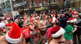 Peserta memulai lomba menyusuri Boylston Street selama Santa Speedo Run di Boston, Massachusetts, Sabtu (14/12/2019). Speedo Run adalah perlombaan lari menjelang Natal dengan peserta pria hanya menggenakan celana dalam dan wanita memakai bikini beserta topi ala Sinterklas. (Joseph Prezioso/AFP)