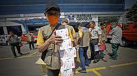 """Relawan menunjukkan beberapa kotak berisi masker yang akan dibagikan kepada masyarakat dalam """"Gerakan Mobil Masker Untuk Masyarakat"""" di Jakarta, Kamis (12/8/2021). (Dok BNPB)"""
