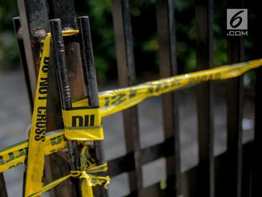 Garis polisi terpasang di pagar rumah korban kasus istri bunuh dan bakar suami serta anak tiri di Jalan Lebak Bulus 1, Kavling 129 B Blok U-15, Cilandak, Jakarta, Selasa (3/9/2019). Korban Pupung dan Dana dibunuh oleh empat orang suruhan di rumahnya. (Liputan6.com/Faizal Fanani)