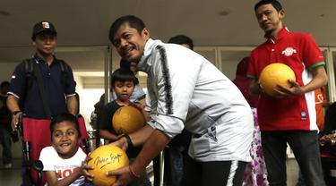 Pelatih Timnas Indonesia U-23, Indra Sjafri, memberikan bola kepada anak-anak yang datang ke Stadion Madya, Jakarta, Rabu (13/3). Sejumlah anak dari Yayasan Rumah Harapan Indonesia datang menemui Timnas U-23 (Bola.com/Vitalis Yogi Trisna)