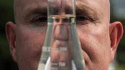 Ahli genetika Universitas Otago Profesor Neil Gemmell berpose dengan wadah air di perairan Loch Ness, Drumnadrochit, Skotlandia, Kamis (5/9/2019). Legenda monster Loch Ness telah ada sejak sekitar 1.500 tahun lalu dan menjadi perbincangan internasional tentang keberadaannya. (Andy Buchanan/AFP)