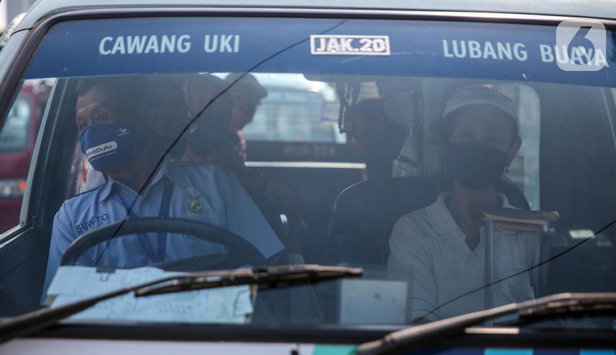 Sopir angkutan umum Jak Lingko mengenakan masker dan sarung tangan di kawasan Cawang, Jakarta, Senin (6/7/2020). Pada perpanjangan masa PSBB transisi, angkutan umum sudah mulai beroperasi kembali dengan menerapkan protokol Kesehatan Covid-19. (Liputan6.com/Faizal Fanani)