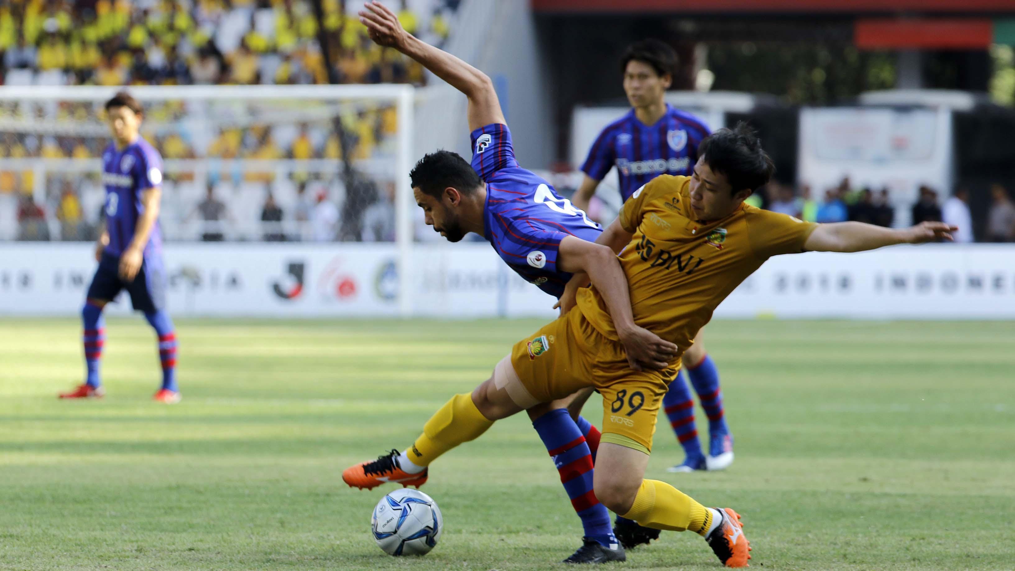 Duel Diego Oliveira (kiri) striker FC Tokyo, dengan Lee Yoo Jun asal Bhayangkara FC dalam laga persahabatan di Stadion Utama Gelora Bung Karno, Senayan Jakarta pada Sabtu (27/1/2018). (Bola.com/Peksi Cahyo)