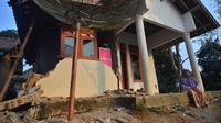 Warga duduk di rumah yang rusak usai gempa melanda Pandeglang, Banten, Sabtu (3/8/2019). Gempa Banten berpusat di kedalaman 48 kilometer Barat Daya Pandeglang. (RONALD SIAGIAN/AFP)
