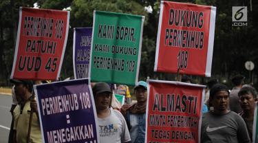 Aliansi Masyarakat Transportasi Nasional membawa spanduk mendukung Permenhub No 108 Tahun 2017 di Kementerian Perhubungan, Jakarta, Kamis (1/2). Mereka menyuarakan dukungan atas diterapkannya Permenhub terkait taksi online ini (Liputan6.com/Arya Manggala)