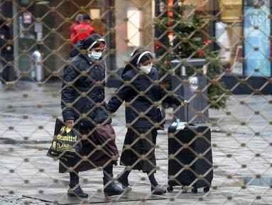 Dua biarawati terlihat berjalan dari balik pagar besi pusat perbelanjaan di Essen, Jerman, Senin (14/12/2020). Jerman melakukan lockdown nasional pada 16 Desember 2020 untuk memerangi pandemi COVID-19. (AP Photo/Martin Meissner)