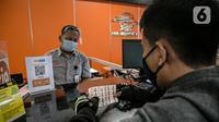 Seorang pria melihat materai Rp. 10.000 di Kantor Pos Pusat, Jakarta, Senin (1/2/2021). Pemerintah menetapkan bea materai Rp 10.000 wajib digunakan untuk dokumen yang dibuat mengenai suatu kejadian yang bersifat perdata. (Liputan6.com/Faizal Fanani)