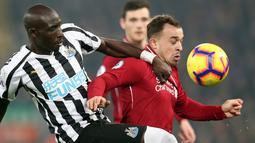 Pemain Newcastle United, Mohamed Diame berebut bola dengan pemain Liverpool Xherdan Shaqiri pada pertandingan Liga Inggris di Stadion Anfield, Rabu (26/12). Liverpool berpesta gol ke gawang Newcastle United, 4-0. (AP/Jon Super)