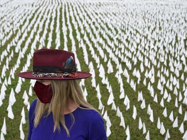 """Seniman Suzanne Brennan Firstenberg berdiri di antara ribuan bendera putih yang ditanam untuk mengenang warga Amerika yang meninggal karena COVID-19 di dekat Stadion RFK di Washington, Selasa (27/10/2020). Instalasi seni publik ini disebut """"In America, How Could This Happen."""" (AP/Patrick Semansky)"""