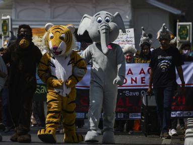 Sejumlah pelajar memakai kostum satwa Indonesia saat melakukan aksi di peringatan Hari Bumi Sedunia di Banda Aceh (22/4). Dalam aksinya para pelajar tersebut membuat karya-karya berupa gambar satwa Indonesia, seperti, orangutan, gajah dan harimau. (AFP Photo/Chaideer Mahyuddin)