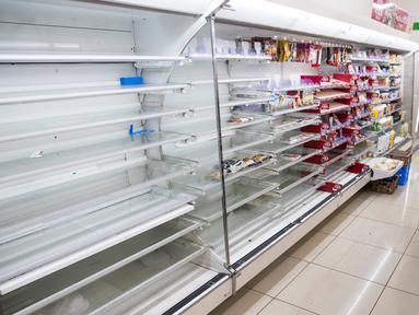 Pembeli memilih bahan makanan dekat rak kosong di sebuah toko, distrik Shinagawa, Tokyo, Sabtu (12/10/2019). Banyak toko-toko perbelanjaan di Jepang yang kehabisan makanan dan minuman akibat warganya yang menimbun makanan untuk menghadapi topan Hagibis. (Odd ANDERSEN / AFP)