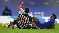 Striker Chelsea, Tammy Abraham (kanan) meringis kesakitan usai dijatuhkan bek Newcastle United, Jamaal Lascelles dalam laga lanjutan Liga Inggris 2020/21 pekan ke-24 di Stamford Bridges, London, Senin (15/2/2021). Chelsea menang 2-0 atas Newcastle. (AFP/Mike Hewitt/Pool)
