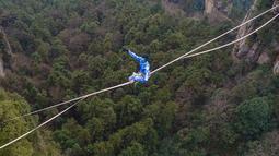 Kontestan berpakaian karakter Avatar bergaya saat melintasi slackline di Pegunungan Huangshizhai di Zhangjiajie, Hunan, China, Minggu (23/12). Pemandangan tersebut memberi sensasi bukit-bukit yang melayang, persis di film Avatar. (STR/AFP)