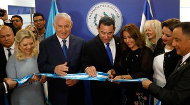 PM Israel Benjamin Netanyahu beserta istri dan Presiden Guatemala Jimmy Morales menyaksikan Ibu Negara Guatemala Hilda Patricia Marroquin memotong pita dalam upacara peresmian Kedubes Guatemala di Yerusalem, Rabu (16/5). (Ronen Zvulun/Pool Photo via AP)
