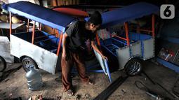 Asep menyelesaikan pembuatan odong-odong di Jakarta, Rabu (30/10/2019). Untuk pembuatan odong-odong jenis kereta mini, Asep mampu menyelesaikan dalam waktu 1 bulan yang dijual dengan harga kisaran Rp 25 juta (3 rangkaian) dan telah menembus pasar hingga luar Jawa. (merdeka.com/Iqbal S. Nugroho)