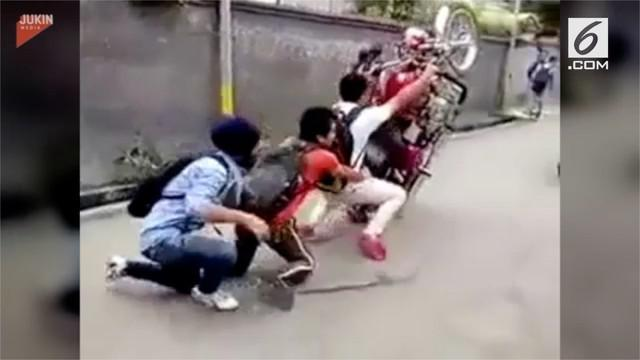Gas tiba-tiba membesar, membuat seorang pria kehilangan kendali. Akibatnya, motor yang ditunggangi oleh tiga pria ini terlepas dan menabrak mobil di depannya.
