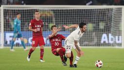 Gelandang Real Madrid, Isco, berebut bola dengan striker Kashima Antlers, Hiroki Abe, pada laga Piala Dunia Antarklub di Stadion Zayed Sports City, Abu Dhabi, Rabu (19/12). Madrid menang 3-1 atas Kashima. (AFP/Giuseppe Cacace)