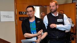 Terdakwa Christian L (kiri) memasuki ruangan sebelum sidang putusan di pengadilan distrik di Freiburg, Jerman, Selasa (7/8). Christian bersama istri mencabuli dan menjual putranya yang masih berusia 10 tahun ke situs paedofil. (THOMAS KIENZLE/AFP)