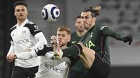 Gelandang Fullham, Harrison Reed berebut bola dengan penyerang Tottenham Hotspur, Gareth Bale pada pekan ke-27 Liga Inggris di Craven Cottage, Jumat (5/3/2021) dini hari WIB. Tottenham Hotspur unggul 1-0 atas Fullham lewat gol bunuh diri Tosin Adarabioyo. (Neil Hall/Pool via AP)