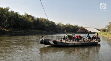 Perahu eretan atau tambangan saat mengantarkan warga menyeberangi Sungai Brantas, Desa Mayan, Mojo, Kediri, Sabtu (29/9). Perahu eretan ini sudah ada sebelum masa penjajahan Belanda. (Merdeka.com/Iqbal Nugroho)