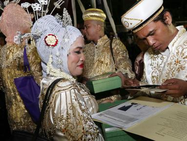 Sejumlah pasangan mengikuti nikah massal di malam pergantian tahun di Jalan MH Thamrin, Jakarta, Minggu (31/12). Sebanyak 430 pasangan melakukan nikah massal yang diselenggarakan oleh pemprov DKI Jakarta. (Liputan6.com/Angga Yuniar)