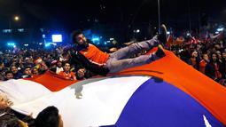 Sejumlah Suporter melemparkan suporter Chili di bendera nasional merayakan kemenangan Chili atas Argentina di final Copa Amerika 2015 di Santiago, (4/7/2015). Chili menang lewat adu penalti atas Argentina dengan skor 4-1. (REUTERS/Rodrigo Garrido)