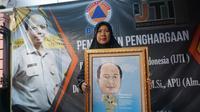 Istri Sutopo sedang menunjukkan karikatur bergambar suaminya yang diberikan IJTI, Kamis (11/7).(Liputan6.com/Fajar Abrori)