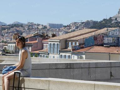 Seorang wanita duduk dengan latar belakang suasana kota di Marseille, Prancis, Minggu (3/7/2016). Marseille merupakan daerah pesisir di selatan Prancis dengan pesona keindahan alam. (Bola.com/Vitalis Yogi Trisna)
