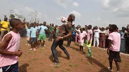 Mantan penyerang Chelsea, Didier Drogba berusaha mengontrol bola saat bermain dengan murid-murid saat peresmian sekolah di Pokou-Kouamekro, dekat Gagnoa, Pantai Gading tengah barat (17/1). (AFP Photo/Sia Kambou)
