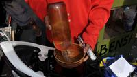 Seorang warga melayani pengisian bensin eceran di kawasan Petamburan, Jakarta, Senin (2/3/2015). Pemerintah kembali menaikkan harga BBM jenis Premium sebesar Rp 200 per liter per 1 Maret 2015 pukul 00.00 WIB. (Liputan6.com/Johan Tallo)
