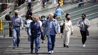 Pejalan kaki dengan masker dan tanpa masker berjalan melintasi Las Vegas Boulevard, di Las Vegas Selasa (27/4/2021). Warga Amerika Serikat (AS) yang telah menerima vaksin COVID-19 tidak lagi diwajibkan mengenakan masker saat berada di luar ruangan jika tidak ada kerumuman. (AP Photo/John Locher)