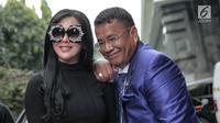 Penyanyi Syahrini berpose bersama pengacaranya Hotman Paris Hutapea sebelum memasuki gedung Bareskrim Polri, Jakarta, Senin (9/10). Syahrini akan menjalani pemeriksaan lanjutan sebagai saksi terkait kasus penipuan First Travel (Liputan6.com/Faizal Fanani)