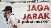 Warga melintas di depan spanduk sosialisasi pencegahan COVID-19 di kawasan Kemang, Jakarta, Kamis (9/7/2020). Berdasar data yang diumumkan pemerintah pada Kamis (9/7) ada penambahan 2.657 orang yang terinfeksi COVID-19 sehingga jumlah penderita menjadi 70.736. (Liputan6.com/Helmi Fithriansyah)