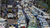 Sejumlah Sopir taksi saat melakukan demo di sepanjang jalan tol Gatot Subroto, Jakarta, Selasa (22/3). Selain melakukan demo supir taxi tersebut melakukan sweeping ke sopir taksi yang beroperasi di dalam tol, dan membakar ban.(Liputan6.com/Johan Tallo)