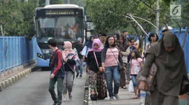 Penumpang menelusuri trotoar usai turun dari bus Transjakarta di Terminal Blok M, Jakarta, Minggu (1/7). Halte bus Transjakarta pertama di Ibu Kota ini kini terlihat kurang terawat dan minim sarana prasarana bagi penumpang. (Merdeka.com/Iqbal S. Nugroho)