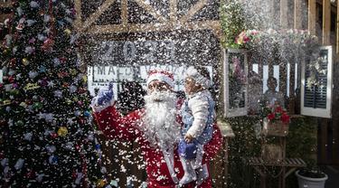 Seorang pramusaji Palestina berpakaian Sinterklas saat berkerja di sebuah restoran di pantai di Kota Gaza, Minggu (13/12/2020). Restoran tersebut didandani dengan tema Natal, pelayanannya pun berpakaian seperti Sinterklas. (AP Photo/Khalil Hamra)