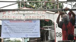 Warga memasang alat penyemprot cairan disinfektan di RW 04 Cipinang Melayu, Jakarta, Minggu (29/3/2020). Selain menutup sebagian jalan dengan seng, warga juga memasang spanduk imbauan dan alat penyemprot disinfektan di dalam gang guna mengantisipasi penyebaran corona. (merdeka.com/Iqbal Nugroho)