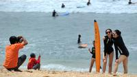 Dua turis wanita berpose saat difoto di pantai Kuta di pulau pariwisata Indonesia di Bali (4/1). Daerah ini merupakan tujuan wisata turis mancanegara dan telah menjadi objek wisata andalan Pulau Bali sejak awal tahun 1970-an. (AFP Photo/Sony Tunbelaka)